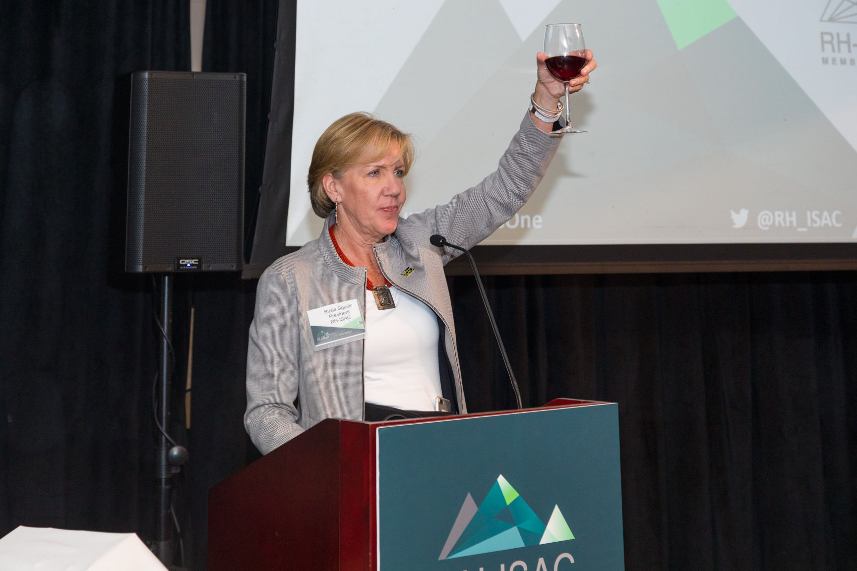 A women in a grey jacket lifts a glass of wine at a podium