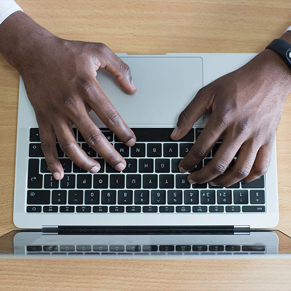 An image of a mans hands resting on laptop keys