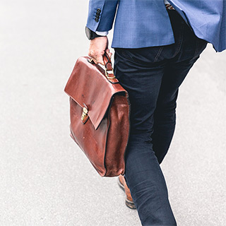 A man carries a briefcase at his side.