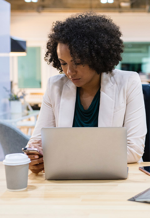 A woman works on her laptop with a disposable cup on the table.