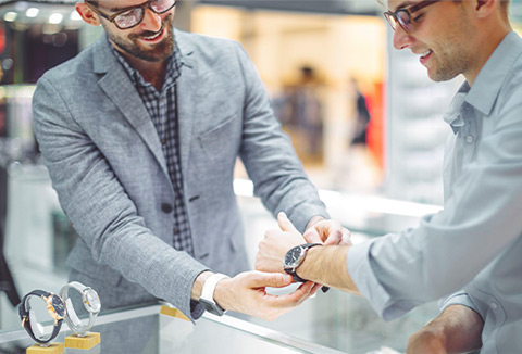 A salesperson assists a customer with a wristwatch.