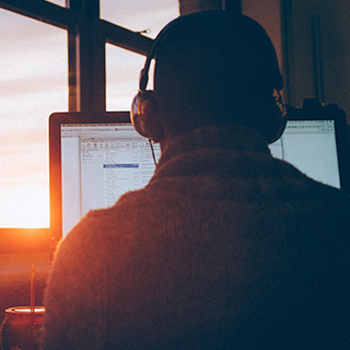 A person wearing large headphones work at a computer while the sun sets