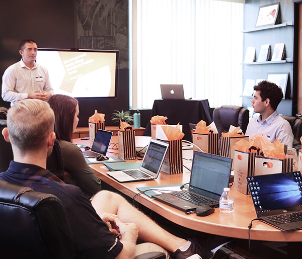 A man stands in front of a conference table with 3 people sitting at it with their laptops in front of them.