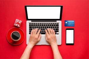 A person rests their hands on their laptop keys with a cellphone, credit card, cup of coffee and small wrapped box around it.